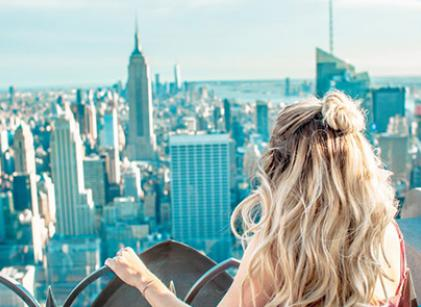 A girl on top of a high city building overlooking the city below.