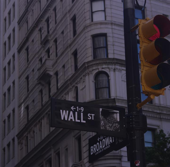 A stoplight at the corner of Broadway and Wall street