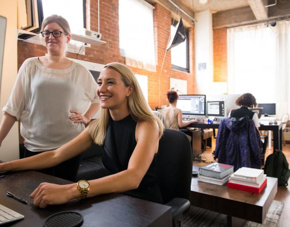 two women looking at a computer monitor in an office