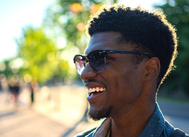 A student smiling on a bright and sunny day outside.