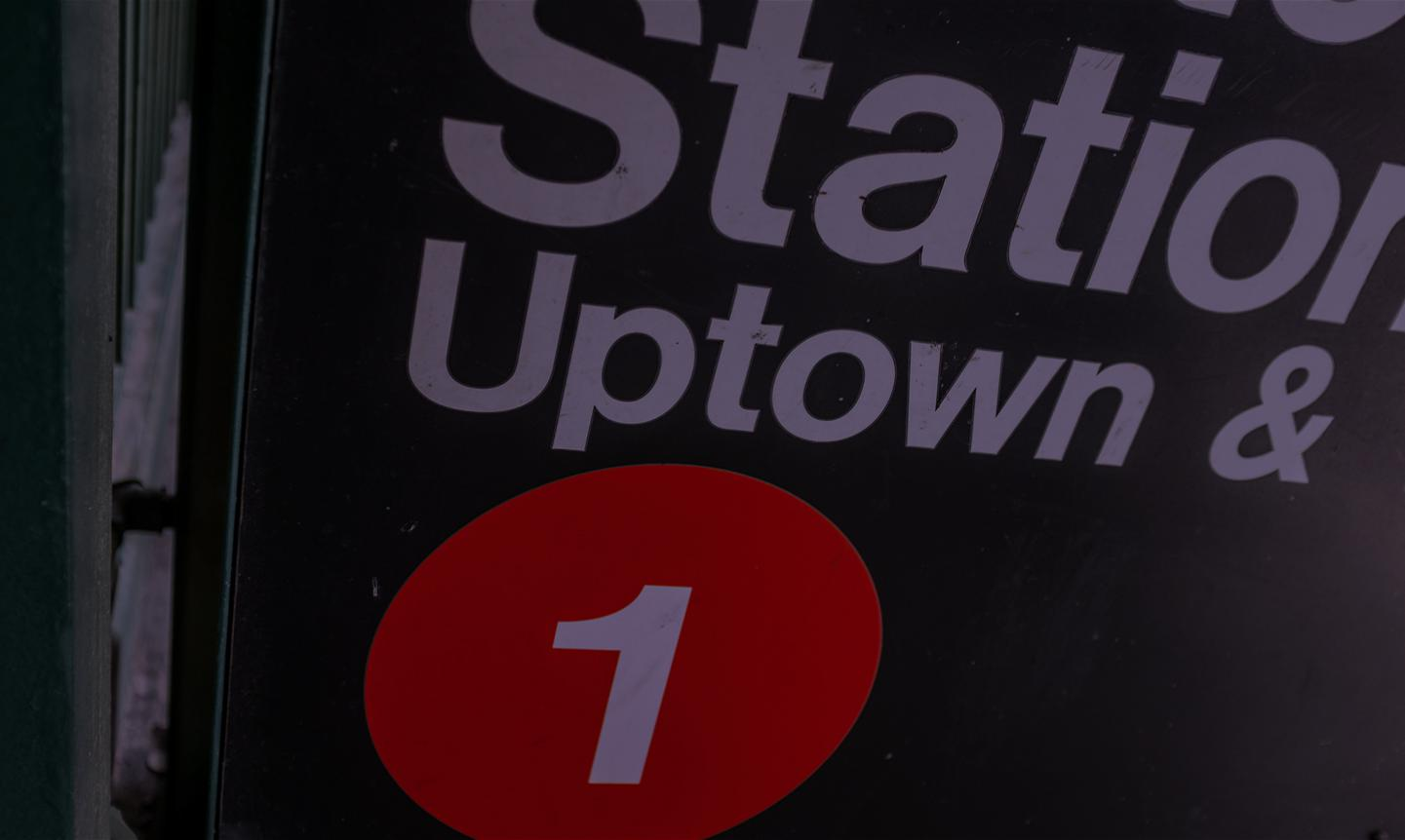 A subway station sign calling out the Uptown stop.